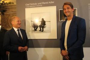 Olaf Scholz und Rene Adler vor ihrem Foto