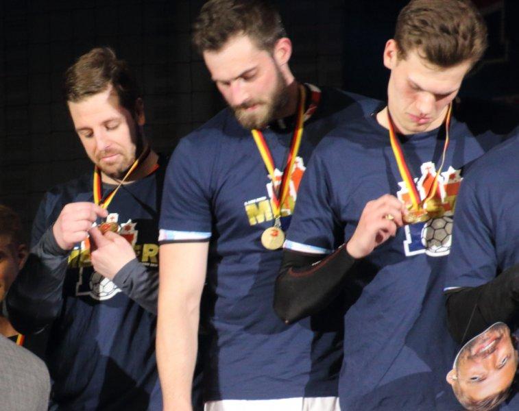 Jan Pevelin, Jan Torben Ehlers und Finn Wullenweber betrachten ihre Medaillen
