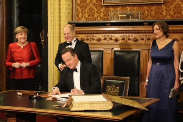 Angela Merkel und David Cameron tragen sich ins Goldene buch der Stadt ein.